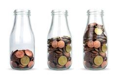 Investissement à l'avenir Bouteilles en verre avec d'euro pièces de monnaie comme le diagramme d'isolement Image stock