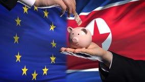 Investissement d'UE en Corée du Nord, main mettant l'argent dans la tirelire sur le fond de drapeau clips vidéos