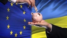 Investissement d'UE en Ukraine, main mettant l'argent dans la tirelire sur le fond de drapeau clips vidéos