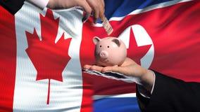 Investissement de Canada dans la main de la Corée du Nord mettant l'argent à l'arrière-plan de drapeau de tirelire banque de vidéos