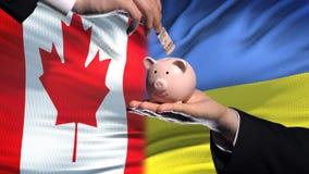 Investissement de Canada en Ukraine, main mettant l'argent dans la tirelire sur le fond de drapeau banque de vidéos