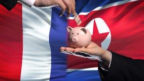 Investissement de Frances dans la main de la Corée du Nord mettant l'argent à l'arrière-plan de drapeau de tirelire banque de vidéos