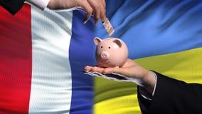 Investissement de Frances en Ukraine, main mettant l'argent dans la tirelire sur le fond de drapeau clips vidéos