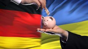 Investissement de l'Allemagne dans la main de l'Ukraine mettant l'argent dans la tirelire sur le fond de drapeau banque de vidéos