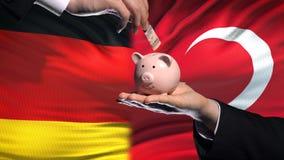 Investissement de l'Allemagne en Turquie, main mettant l'argent dans la tirelire sur le fond de drapeau banque de vidéos