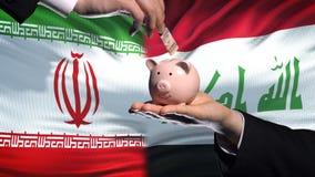 Investissement de l'Iran en Irak, main mettant l'argent dans la tirelire sur le fond de drapeau banque de vidéos