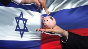 Investissement de l'Israël en Russie, main mettant l'argent dans la tirelire sur le fond de drapeau banque de vidéos
