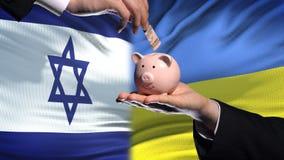 Investissement de l'Israël en Ukraine, main mettant l'argent dans la tirelire sur le fond de drapeau banque de vidéos
