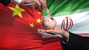 Investissement de la Chine en Iran, main mettant l'argent dans la tirelire sur le fond de drapeau banque de vidéos