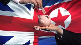 Investissement de la Grande-Bretagne dans la main de la Corée du Nord mettant l'argent dans la tirelire, finances banque de vidéos