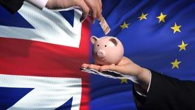 Investissement de la Grande-Bretagne dans la main d'UE mettant l'argent dans la tirelire, fond de drapeau banque de vidéos