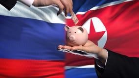 Investissement de la Russie dans la main de la Corée du Nord mettant l'argent à l'arrière-plan de drapeau de tirelire clips vidéos