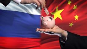 Investissement de la Russie en Chine, main mettant l'argent dans la tirelire sur le fond de drapeau banque de vidéos