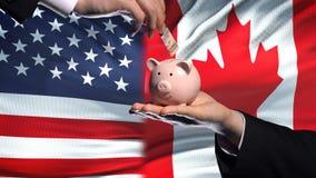Investissement des USA dans le Canada, main mettant l'argent dans la tirelire sur le fond de drapeau clips vidéos