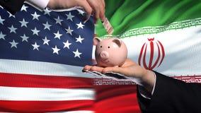 Investissement des USA en Iran, main mettant l'argent dans la tirelire sur le fond de drapeau banque de vidéos
