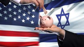 Investissement des USA en Israël, main mettant l'argent dans la tirelire sur le fond de drapeau banque de vidéos