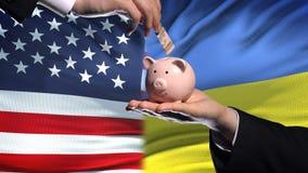 Investissement des USA en Ukraine, main mettant l'argent dans la tirelire sur le fond de drapeau banque de vidéos