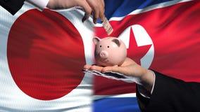 Investissement du Japon dans la main de la Corée du Nord mettant l'argent dans la tirelire, fond de drapeau banque de vidéos