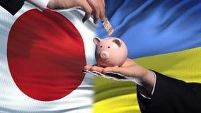Investissement du Japon en Ukraine, main mettant l'argent dans la tirelire sur le fond de drapeau banque de vidéos