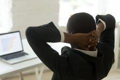 Investisseur sûr africain s'asseyant sur le lieu de travail avec le behin de mains Photo stock