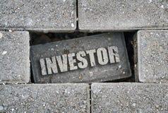 Investitore di parola sopra un mattone fotografia stock