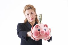 Investment. Business lady holding a piggy bank with onehundred US dollar to the camera. Focus on piggy bank, woman out of focus Stock Image