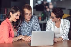 Investment adviser giving a presentation to a friendly smiling young couple seated at her desk in the office royalty free stock images