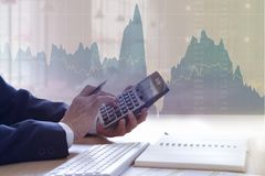 Investment Analysis. Businessman in the office touching calculator buttons for investment analysis with area and line graph in background Stock Photo