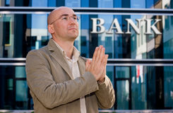 Investment banker praying. Man looking up and praying - bank sign in background Royalty Free Stock Photo