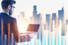 Investment and banking concept. Businessman using laptop on abstract city background with glowing forex chart. Investment and banking concept. Double exposure Royalty Free Stock Image