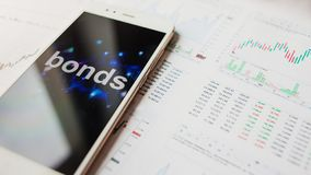 Investment in bonds, conservative investment concept. Reports and statistics,. Analysis of the corporate securities market. Smartphone with an inscription on stock image