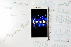 Investment in bonds, conservative investment concept. Reports and statistics,. Analysis of the corporate securities market. Smartphone with an inscription on royalty free stock photography