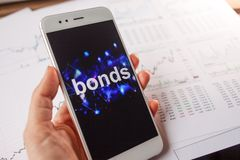 Investment in bonds, conservative investment concept. Reports and statistics,. Analysis of the corporate securities market. Smartphone with an inscription on stock images