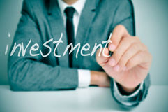 Investment. Businessman sitting in a desk writing the word investment in the foreground Royalty Free Stock Photo
