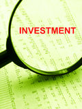 Investment concept. A conceptual picture of the word investment placed within a magnifying glass, over a financial document showing share prices in a stock Stock Photos