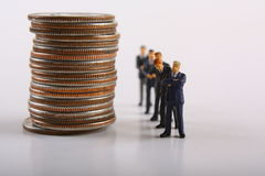 Investment Concept. Line of miniature businessmen standing next to a stack of quarters Stock Images