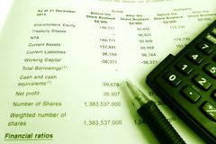 Investment concept, share holders annual report. A photograph of investing in shares concept, showing a pen and calculator placed on top of  an open page of a Stock Images