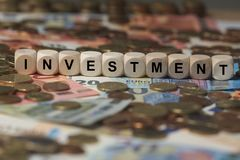 Investment - cube with letters, money sector terms - sign with wooden cubes. Series of cube with letters from money sector Stock Image