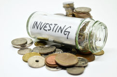 Investment lable in a glass jar with coins spilling out Stock Photos