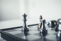 The king chess piece with chess others. Investment Leadership Concept : The king chess piece with chess others nearby go down from floating board game concept of Royalty Free Stock Photos