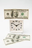 Investment of money into time. Financial concept. Investment of money into time. Notes of the USA of dollars near white hours Royalty Free Stock Image