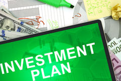 Investment plan. Tablet with words investment plan with dollars and euro. Business concept Stock Photography