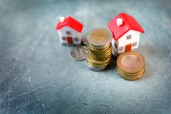 Investment in real estate and rising of houses price concept. Small model house with red roof surrounded by coins. Investment in a real estate and rising of stock photography