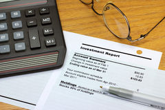 Investment Report. An investment report on a desk with a calculator, eye glasses, and a pen Royalty Free Stock Images