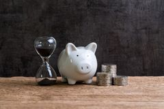 Investment and saving time concept by hourglass or sandglass wit. H white piggy bank and coins stacked on wood table with black background Royalty Free Stock Photo