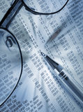 Investment scrutiny. Close-up of pen and glasses on financial newspaper Stock Photo