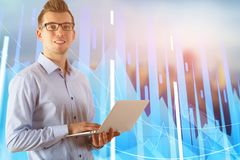 Investment and stock exchange concept. Attractive smiling european businessman using laptop on blurry city background with forex chart. Investment and stock stock images