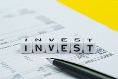Investment, stock market and mutual fund concept, small cube block with alphabets building the word Invest on market profit and. Loss report paper with pen on royalty free stock images