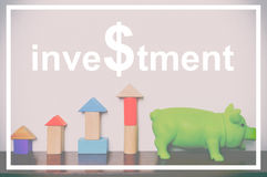 Investment text with toy block rising graph and piggy bank royalty free stock photos
