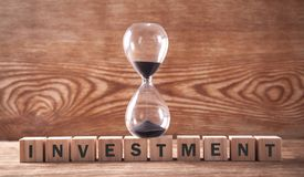 Investment text on wooden cubes with hourglass. Time to invest royalty free stock image